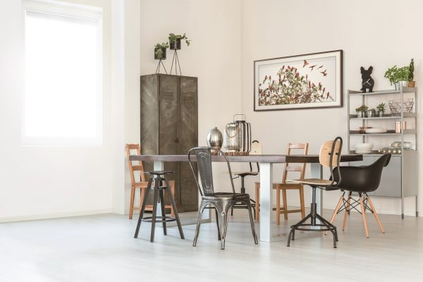 Trendy, white dining room with table, chairs, cart and lamp