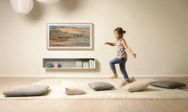 Girl in living room walking across cushions, Munich, Bavaria, Germany